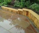 Oak retaining bench with sandstone paving and setts.