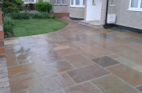 Mixed earthy colours with cobble edging for this Indian sandstone driveway.