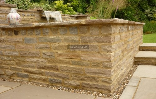 Multi sized sandstone pond wall.