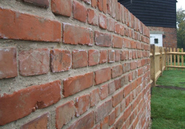 A double wall built from old reclaimed bricks using English bond method.