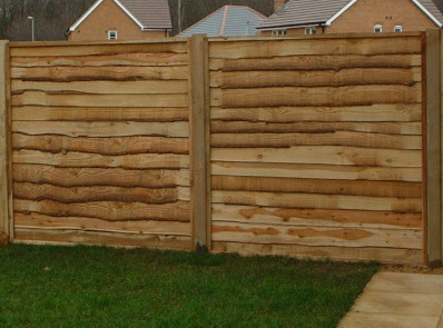 Pressure treated softwood waney overlap panels on 4'' x 4'' posts.