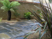 Antique black indian sandstone patio with hints of brown to compliment the boundary wall.