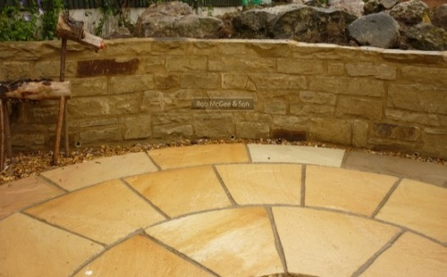 Sand stone circle against Yorkstone walling.